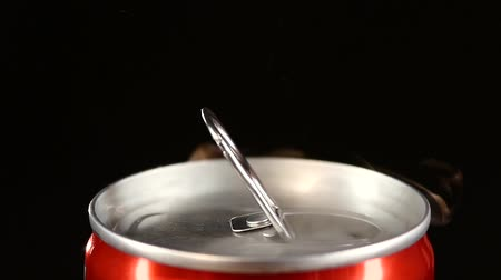 může : A hand opening red can, isolated on black background, slow motion