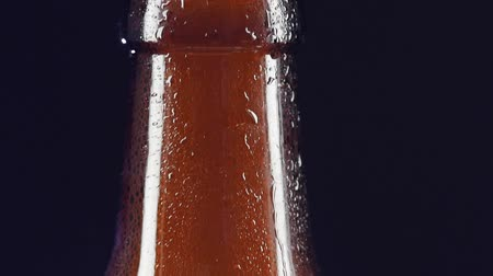 şişeler : Opening drink bottle with bottle opener on dark background, slow motion, cam moves upwards, spray, splash