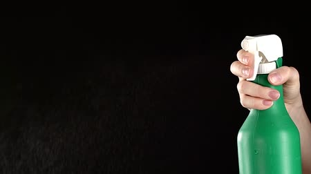 pulverização : Hand holds white-green spray bottle, on black background, slow motion Stock Footage