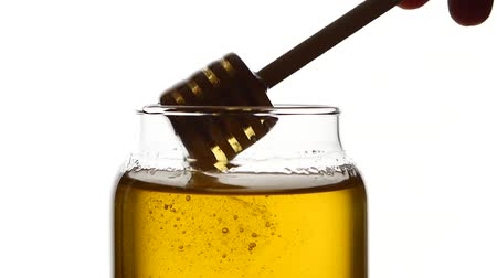 drizzler : Glass jar of honey with wooden drizzler, pick it up, isolated on white background, slow motion, close up