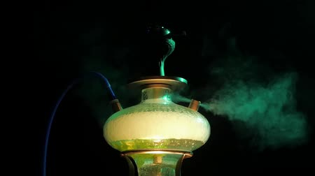 sivilceli : Colored yellow hookah with the smoke, Details of hookah in the lounge caffee. close up. slow motion