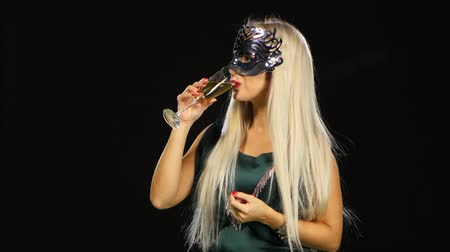 маскарад : Sexy model woman with glass of champagne wearing venetian masquerade mask at party, drinking champagne over holiday glowing background. Christmas and New Year celebration, black background