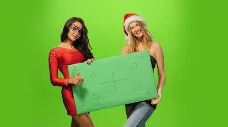 irmãs : A pretty young brunette and blond womans in Santa hats, At Christmas Time. green blank sign, green screen