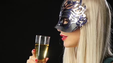 ruj : Sexy model woman with glass of champagne wearing venetian masquerade mask at party, drinking champagne over holiday glowing background. Christmas and New Year celebration, black background, Slow motion, close up