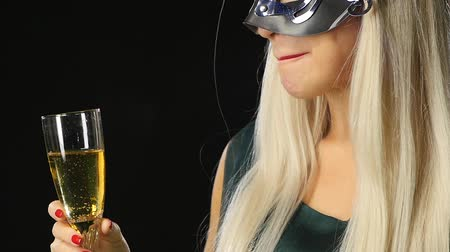 маскарад : Sexy model woman with glass of champagne wearing venetian masquerade mask at party, drinking champagne over holiday glowing background. Christmas and New Year celebration, black background, Slow motion, close up