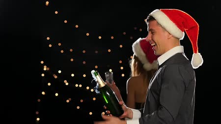 šampaňské : Young happy couple opening champagne on New Years eve. Beautiful woman and man in Christmas cap, isolated on Black, Bokeh, sexy blonde, lose up. Slow motion