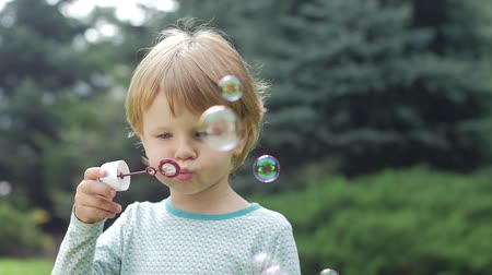 bright bubble : Little happy girl blowing soap bubbles in the park. Summer joy - lovely girl, happy child concept. Slow motion. Close up Stock Footage