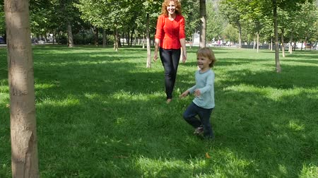 испанец : Happy young mother with her daughter at park. Cheerful mother rotating twisting making circle with her little daughters. Happy Family on a Walk in Summer. Slow motion Стоковые видеозаписи
