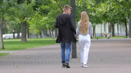 zakochana para : Young couple in love walking together hand by hand in park, back view. slow motion