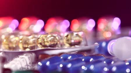 addiction recovery : Top of syringes lays on some different colorful contraceptive pills, rotation, reflection, and close up, on black background, back light like red and blue Stock Footage