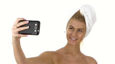 dudak : beautiful sexy woman with a towel on her head takes selfie with her phone. Close up, bathroom