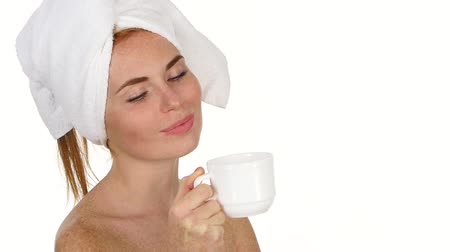 arcszín : Attractive healthy girl is drinking coffee. She is standing and gently smiling. Her eyes are closed with pleasure and she has towel on her head. Isolated on white background. slow motion Stock mozgókép