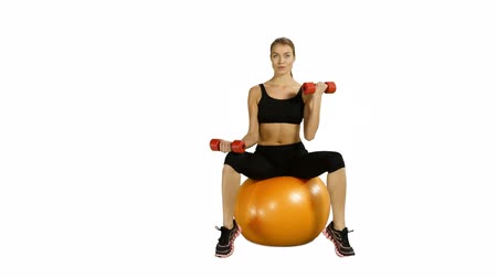 oturma : Beautiful girl sitting on pilates ball and exercising with dumbbells. white background. Looking at camera, Gym