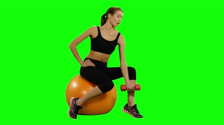 бицепс : Beautiful girl sitting on pilates ball and exercising with dumbbells. Green background. Looking at camera, Gym