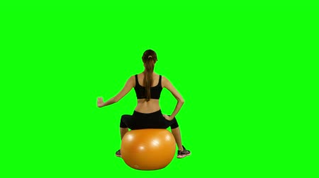 zadní : Young happy woman doing fitness exercise with fitness-ball, isolated on green background, Gym Dostupné videozáznamy