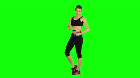 latino americana : Woman taking body measurements - isolated over a green , sportswear
