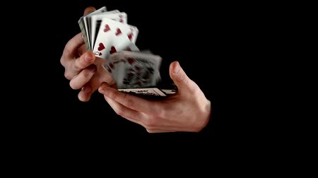маг : Magician shuffling the cards, on black background, slow motion