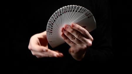 trik : Talanted magician showing his trick with usual cards, like fan on black background, close up, slow motion