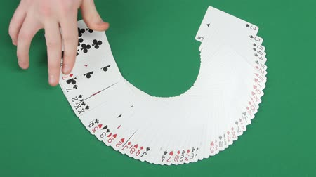 цирк : Playing cards being spread round on a green surface by magician, trick with cards