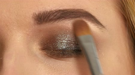 косметика : Beautiful model applying eyeliner closeup on eye, Close up, Make-up artist applying bright base color eyeshadow on models eye and holding a shell with eyeshadow