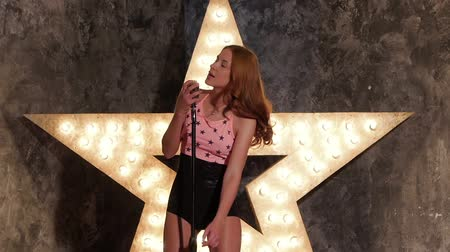 vokální : Beautiful young female vocalist in holding vintage microphone, playful smile, preparing to sing during musical show, shining star in the background. slow motion