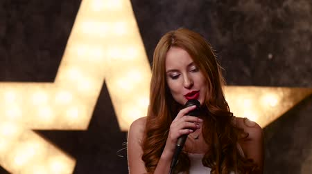 singers : Stylish girl singing with a microphone, closed eyes singing, female singer with microphone, music hall, the scene, shining star in the background, slow motion, close up, silhouette
