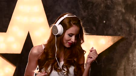 kopya : attractive smiling teen girl with headphones, Shot in a studio. Attractive brunette woman recording a song in music studio, Woman listening to music on headphones, portrait of beautiful girl. slow motion, silhouette. close up Stok Video