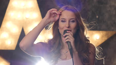 musicians stage : Attractive steam punk, Portrait of female rock singer with red lips and microphone, music hall, the scene, shining star in the background, close up Stock Footage