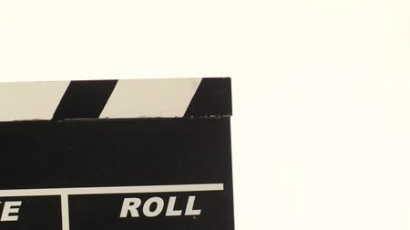 yönetim kurulu : Person uses movie clapper board, on white, close up Stok Video