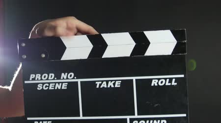 klipek : Hands holding a film clapper board, on black, close up, back light