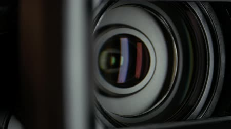 videocamera : Video camera lens, showing zoom and glare, turns, close up