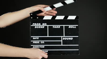 film slate : Hands use movie production clapper board, on black, slow motion