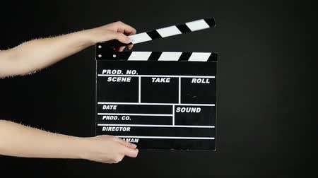 film slate : Hands with movie production clapper board, on black, slow motion