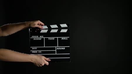 film slate : Hands with movie clapper board, on black, slow motion
