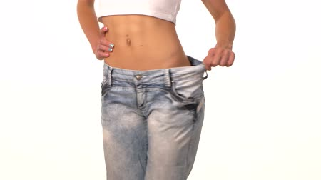 fogyás : Slim girl in big jeans, showing her lose weight, on white