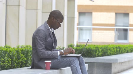 afro americana : american businessman working with glasses on laptop outdoors on a background of corporate building