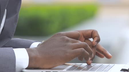 usuário : american businessman Cropped hand of man holding mobile phone while typing on laptop. Close up Stock Footage