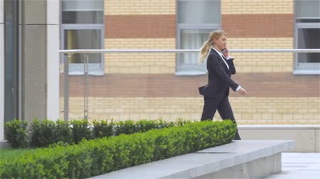 notebooklar : Successful woman talking on cellphone while walking outdoor.  slow motion