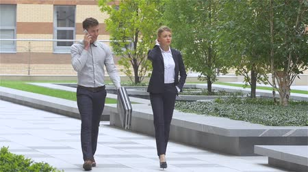 executivo : Two successful business colleagues walking on the street of an business center. slow motion