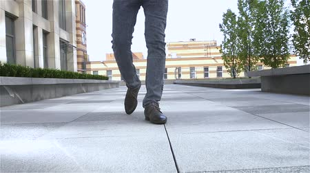 man foot with brown leather shoes and jeans, slow motion