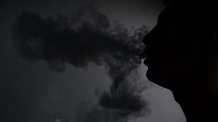 carcinogenic : Man smoking electronic cigarette on black, silhouette