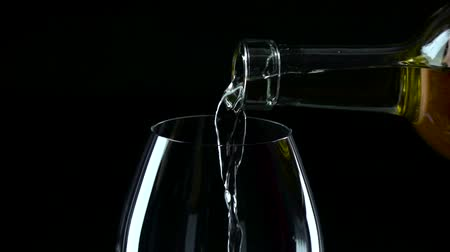 espumante : White wine being poured into a wineglass, black, slowmotion, closeup