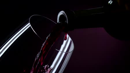 alcohol : The bottle of wine, the wine is poured into a glass, black, closeup, slowmotion