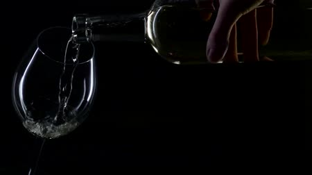 na zdraví : White wine being poured into a wine glass, silhouette, black , slowmotion