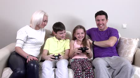 eğlence oyunları : Positive family playing video games together in a living room Stok Video
