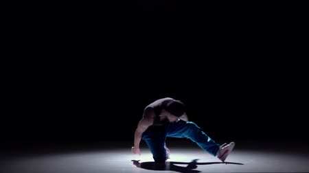 хоп : Talanted dancer in blue trousers starts dancing breakdance, on black, shadow, slow motion