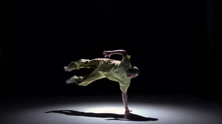 biodro : Breakdance dancer in yellow suit continue dance on black, shadow, slow motion