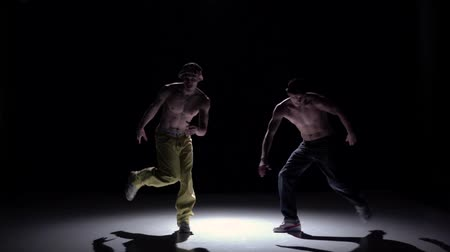 biodro : Two talanted dancers dance breakdance and turning around on black, shadow, slow motion