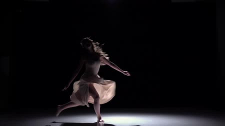 gracioso : Modern dancer girl in white dress starts dancing contemporary on black, shadow, slow motion Vídeos