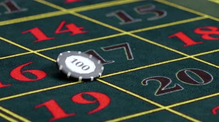 usual : Croupier twists one usual chip on green table at casino